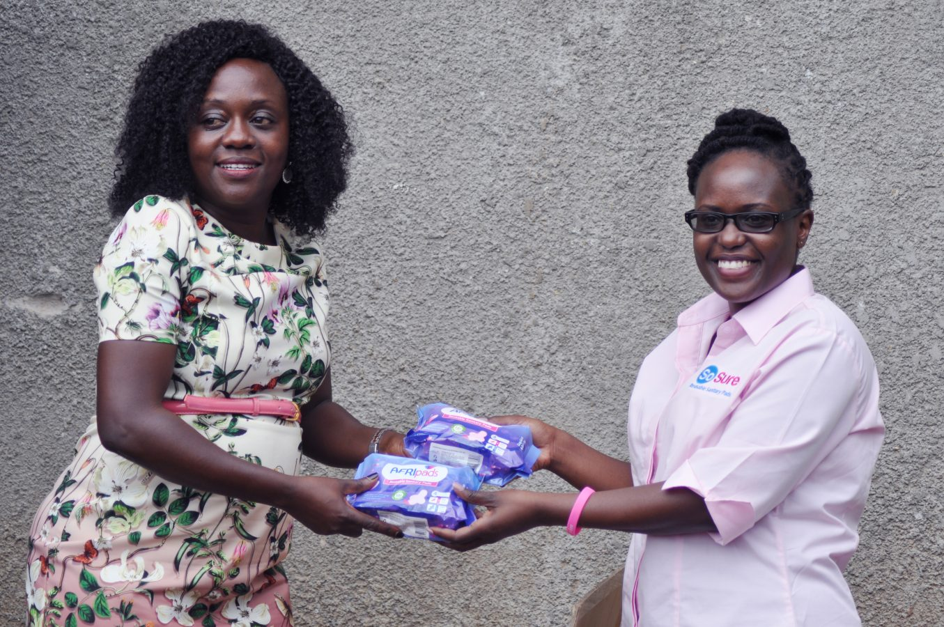 Madam Judith recieving pads from Afripads staff.